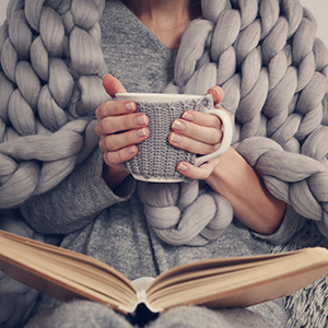 Woman with coffee book and blanket
